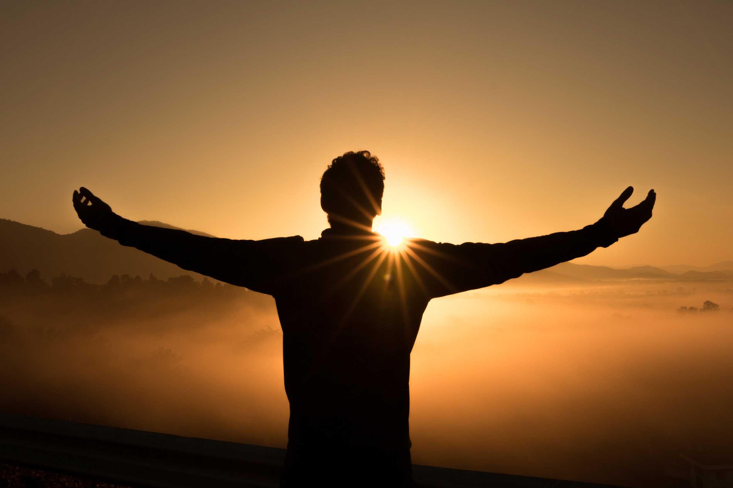 Man standing infront of sunrise