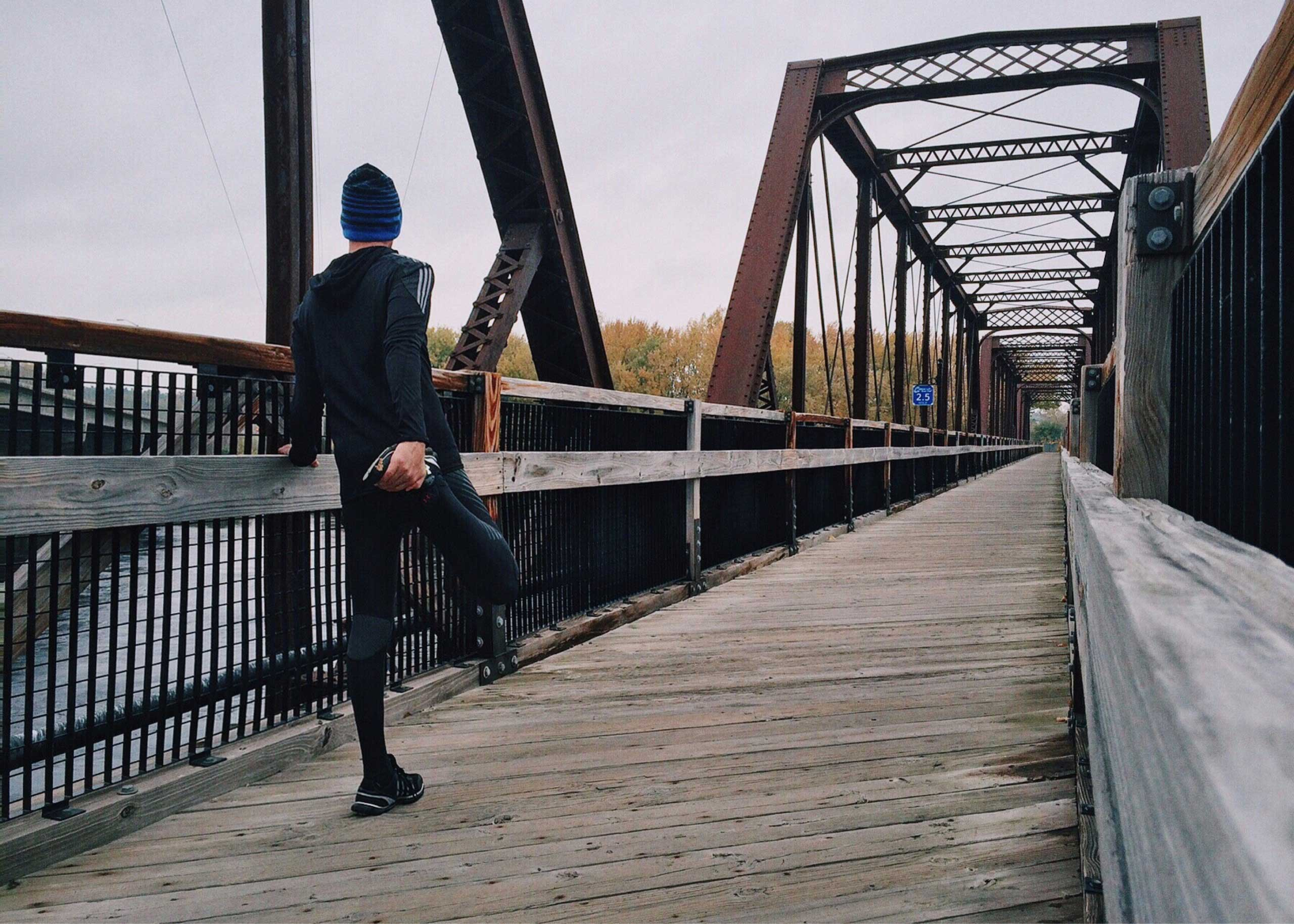 Runner stretching on a bridge