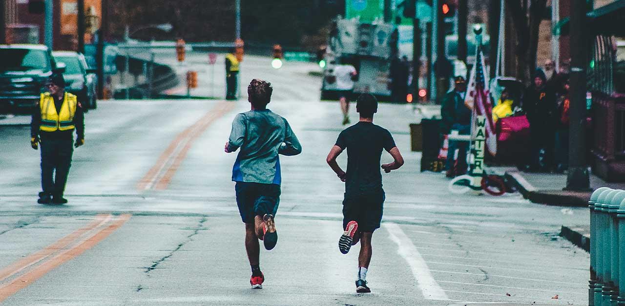 Two men running in the rain