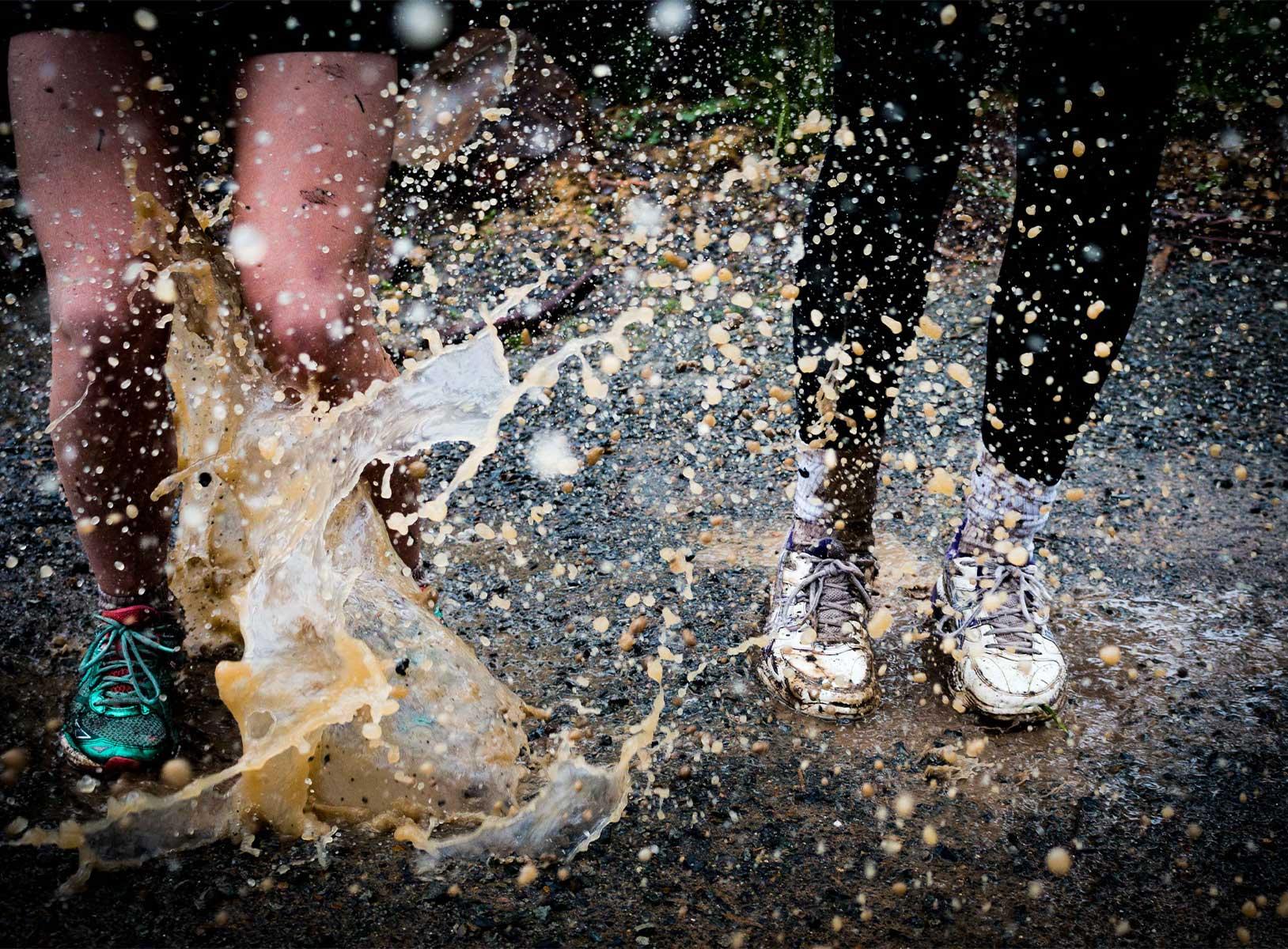 Two people splashing in puddles while running